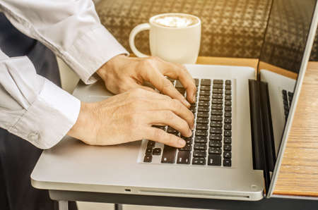 Close up of a man hands typing in a laptop in a coffee shop terrace in the street