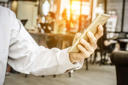 young man working from coffee shop using smart phone , mans hands using smart phone in interior. Stock Photo