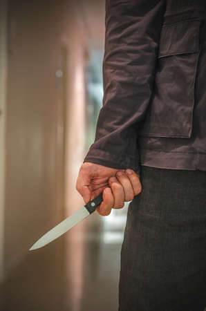 Killer with knife close-up on dark background