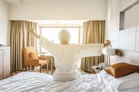 A young man waking up in bed and stretching his arms Stock Photo