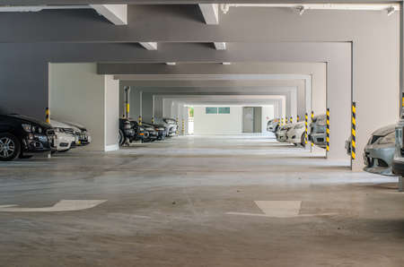 Many cars in parking garage interior building.