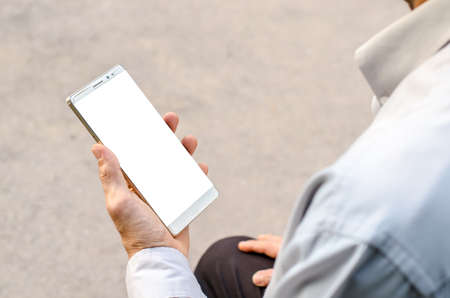 Man uses his Mobile Phone is outdoor park, close up Stock Photo