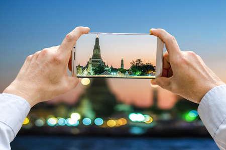 Cropped shot view of mans hands making photo on mobile phone camera of Wat Arun Ratchawararam (Temple of Dawn) with Chaophraya river,bangkok thailand