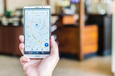 THAILAND, BANGKOK - APRIL 18 2017: een hand met een Huawei mobiele telefoon die de Google Maps-app, met Thailand, weergeeft. Illustratief redactioneel beeld op een interieur achtergrond.