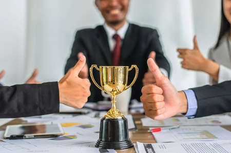 winning business team gold trophy , business team happy consent and successful business team rewarded for in the office