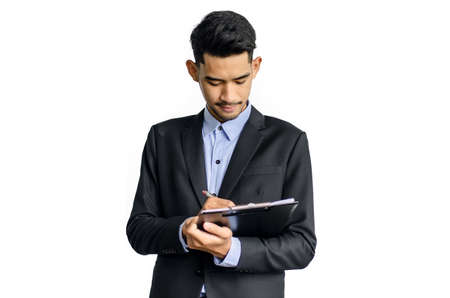 Business man with relaxed look writing on clipboard over white background