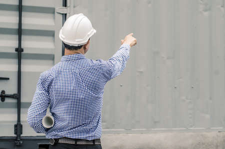 Male architect and blueprints with white helmet pointing finger on a construction site,Architects on construction site check documents and business workflow Stock fotó