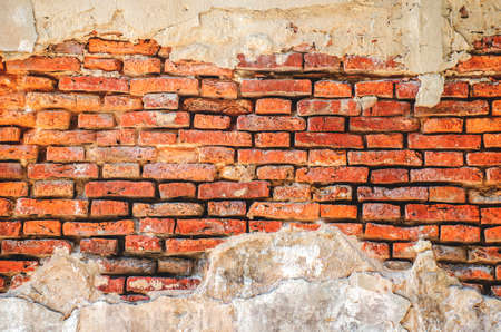 old plastered brick wall with crumbling plaster texture urban background Archivio Fotografico