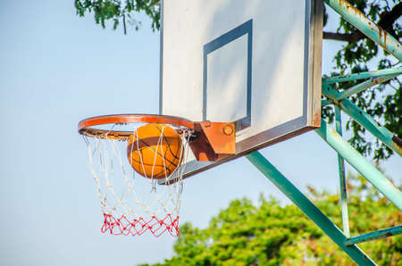 Ball Going Into the Net of the Basket in an Outdoor Basketball Court in evening from the Park,