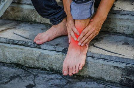 Primer plano joven que siente dolor en el pie debido a calambres en las piernas y tobillos en la escalera, tiene dolor en el tobillo, concepto de salud