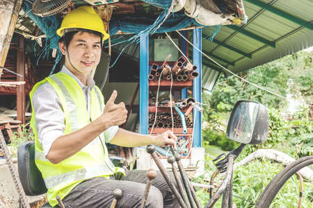 Portrait of a male developer sitting operator driving excavator at construction site.
