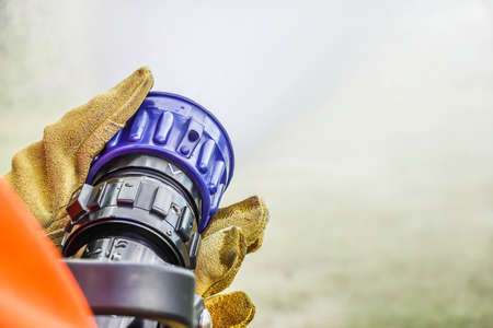 Cropped image of two pairs of hands holdinhg the handle on the end of a fire fighters water hose spraying water during practice at fire station