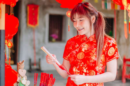 Portrait charming beautiful asian woman wear cheongsam dress up choose buy the incense, in the Chinese New Year. Festivities, New Year Celebration