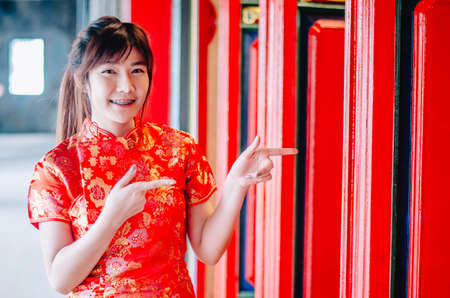Chinese girl in traditional Chinese cheongsam pointing at china temple and introduce something to you in chinese new year Stock Photo - 116637391