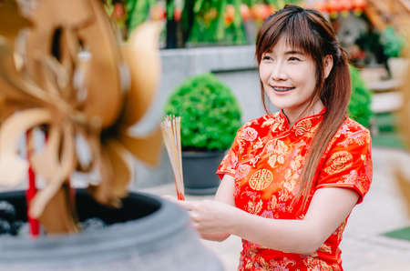 Cute chinese girl dressing traditional red Cheongsam suit burning incense sticks and pay respect and praying to Chinese God for lucky Banque d'images - 116637407