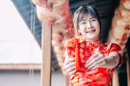 Portrait charming beautiful asian woman wear cheongsam dress up holding red envelop to the camera, The symbol of Chinese New Year. select focus asian woman. Stock Photo