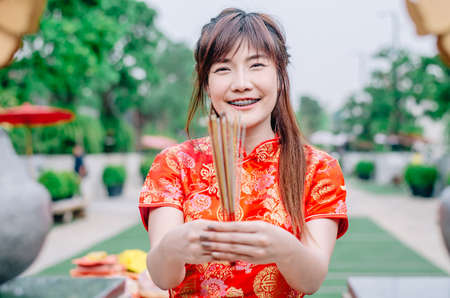 Cute chinese girl dressing traditional red Cheongsam suit burning incense sticks and pay respect and praying to Chinese God for lucky Banque d'images - 116637646