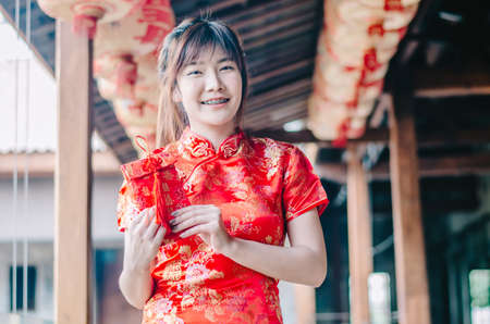 Portrait charming beautiful asian woman wear cheongsam dress gets red envelopes from her family. Pretty girl shows red envelopes. Gorgeous girl feel happiness and she has nice smile. Banque d'images - 116637807