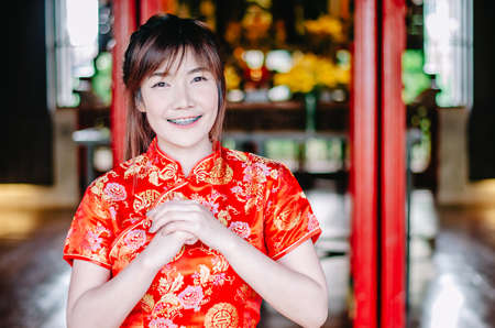 Portrait pretty woman in cheongsam qipao red dress making salute , in the Chinese New Year. Festivities, New Year Celebration