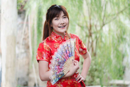 Portrait beautiful young woman smile wear cheongsam deep red dress holding a fan looking camera. Festivities and Celebration concept Stock Photo