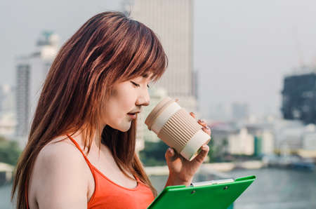 Young Woman Holding the Cup Of Coffee drinking and holding data on Clipboard in city Banque d'images - 116637964