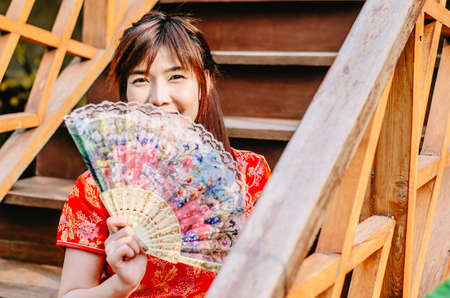 Portrait beautiful young woman smile wear cheongsam deep red dress holding a fan siting on stairs in sexy pose,in the Chinese New Year. Festivities, New Year Celebration