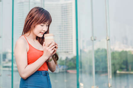 Beautiful young woman standing on balcony having cup of coffee, enjoying sun on a hot summer day. Asia female on terrace with city view in background