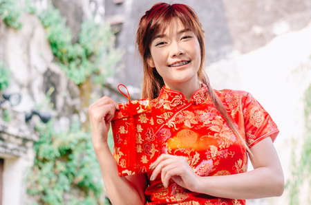 Portrait charming beautiful asian woman wear cheongsam dress gets red envelopes from her family. Pretty girl shows red envelopes. Gorgeous girl feel happiness and she has nice smile.