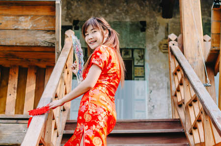 Portrait beautiful young woman smile wear cheongsam deep red dress holding a fan standing on stairs in sexy pose, Festivities and Celebration concept Banque d'images - 116638139