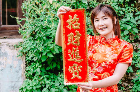 Asian women in festive costumes showing red couplets with chinese happy chinese new year and hope you get rich