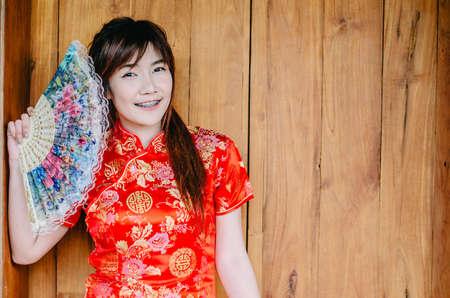 Portrait beautiful young woman smile wear cheongsam deep red dress holding a fan looking camera. Festivities and Celebration concept Reklamní fotografie