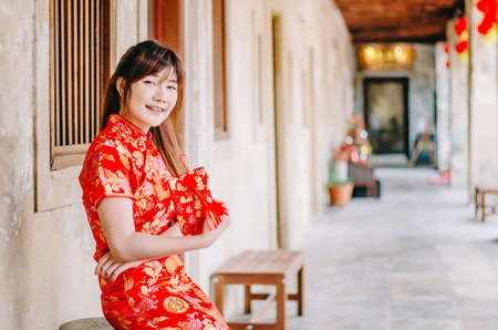Young asian beautiful girl in chinese traditional red dress smile posing sit on the chair, in the Chinese New Year. Festivities, New Year Celebration Stock Photo