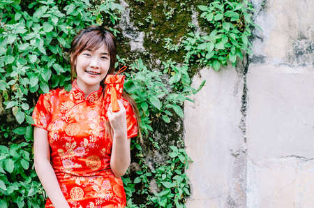 Portrait charming beautiful asian woman wear cheongsam dress gets red envelopes from her family. Pretty girl shows red envelopes. Gorgeous girl feel happiness and she has nice smile. Banque d'images - 116638161