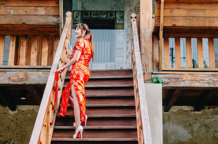 Portrait beautiful young woman smile wear cheongsam deep red dress holding a fan standing on stairs in sexy pose, Festivities and Celebration concept Stock Photo