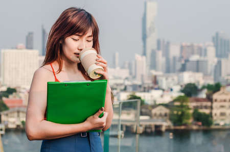 Young Woman Holding the Cup Of Coffee drinking and holding data on Clipboard in city Banque d'images - 116638169