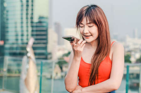 Happy confident woman talking on the mobile cell phone on speakerphone over city background