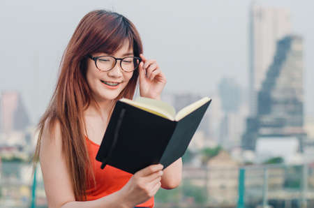 Smiling Young beautiful asian women in glasses reads book in summer city background