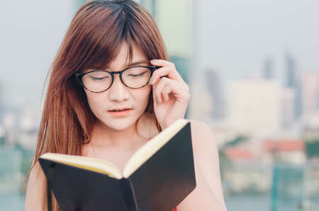 Closeup portrait of attractive female with eyeglasses in hand. Poor young girl has issues with vision. She suffering eyestrain reading a book wearing eyeglasses over city background