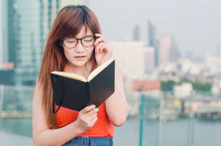 Closeup portrait of attractive female with eyeglasses in hand. Poor young girl has issues with vision. She suffering eyestrain reading a book wearing eyeglasses over city background Banque d'images - 116638230