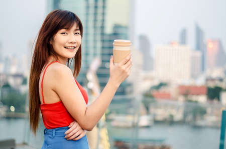 Rear view of a smiling young woman standing at bangkok skyline with a cup of coffee after working in the evening.