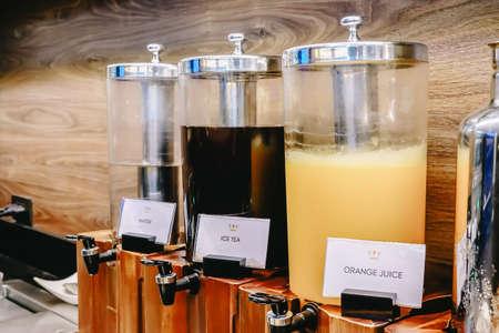 breakfast buffet line, various of beverages tank, orange juice, ice tea, water, in restaurant
