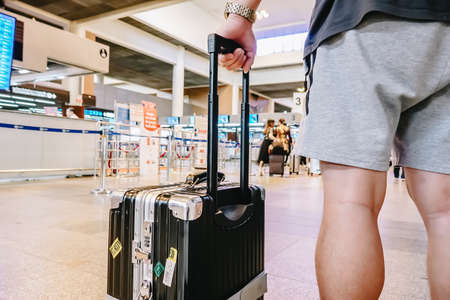 Man standing with luggage at airport. man looking at lounge looking at airplanes while waiting at boarding gate before departure.