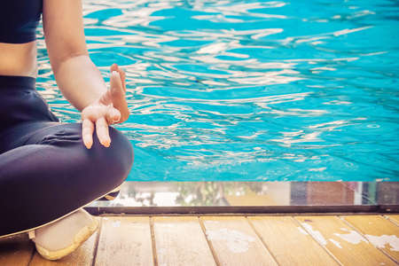 Woman meditating in a lotus yoga position at blue swimming pool
