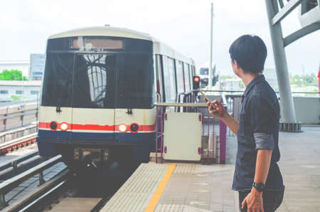 Asian man passenger using smartphone and looking at the train in train station ,skytrain
