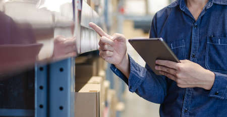 Asian manager man doing stocktaking of products management in cardboard box on shelves in warehouse using tablet. Male professional assistant checking stock in factory. Physical inventory count.