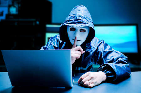 Anonymous computer hacker in white mask and hoodie. Obscured dark face making silence gesture try to hack and steal information system data from computer with usb thumb drive on dark background, Data thief, internet attack.