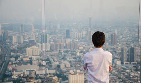 Man standing on roof and looking on city through the window Standard-Bild