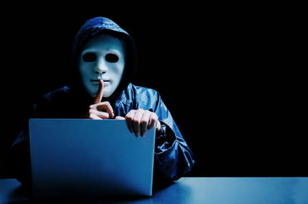 Anonymous computer hacker in white mask and hoodie. Obscured dark face making silence gesture on dark background, Data thief, internet attack, darknet and cyber security concept.