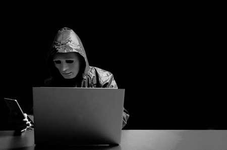 Pirate informatique anonyme en masque blanc et sweat à capuche. Visage sombre obscurci attaquant les gens via un smartphone. contacter victom par SMS et demander plus d'argent, voleur de données, attaque Internet, concept de darknet et de cybersécurité.