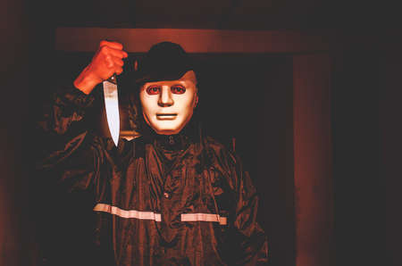 murder, kill and people concept - Criminal or murderer in black wearing a white mask holding knife inside a condo at crime scene 写真素材